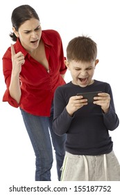Little boy playing with mother's mobilephone, angry mother warning with finger.
