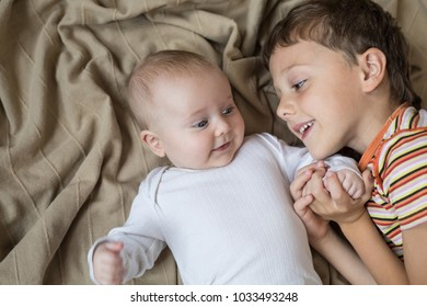 little boy playing with newborn on the bed  at the day time