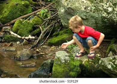 A little boy playing next to a creek.