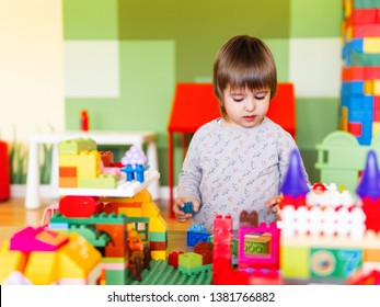 Little boy playing in nurseroom with colorful constructor. Educational toy block in toddler hands. Kid is busy with toy bricks.