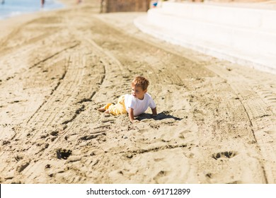 Little boy playing on a beach in summer vacation