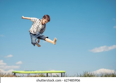 Little boy playing on the field at the day time. People having fun outdoors. He jumping on trampoline on the lawn. Concept of friendly family.