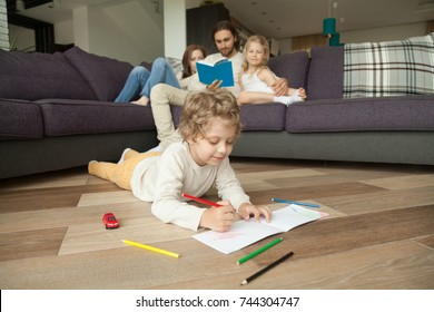 Little boy playing on floor drawing with colored pencils while parents and girl daughter reading book on couch, family spending time together in living room, hobbies activities with kids at home