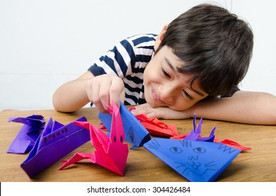 Little boy playing on paper art origami
