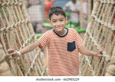 Little boy playing on the rope inddor playground with smile