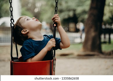 Little boy playing on the swing outdoors