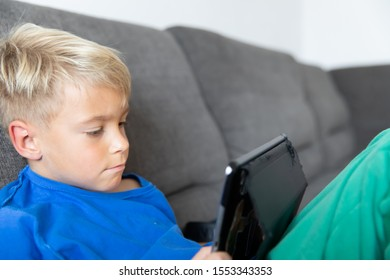 Little boy playing on tablet. The child spends his free time with modern technology.