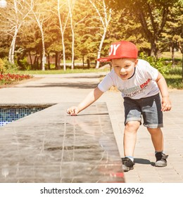 Little boy playing outdoors in the city in park, wheels toy car on a marble surface