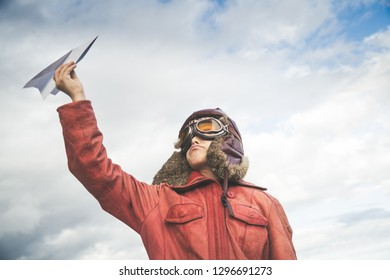 Little boy playing with a paper plane in a sunny day, dreaming about  being an airplane pilot dressed as a vintage aviator Young and happy  kid with an hat thinking about planes and pilots.