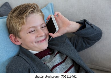 Little boy playing with phone on couch