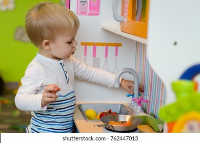 Little boy is playing in the preparation of a meal on a plastic toy kitchen