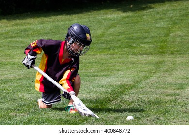 Little boy playing in protective gear lacrosse in the park