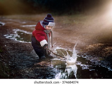 Little boy playing in puddle in spring forest.