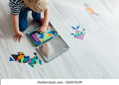 Little boy playing with puzzle on the floor