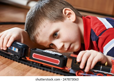 Little boy playing with railway lying on the floor