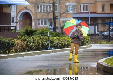 Little boy playing in rainy summer park. Child with colorful rainbow umbrella, waterproof coat and boots jumping in puddle and mud in the rain. Kid walking in autumn shower Outdoor fun by any weather.