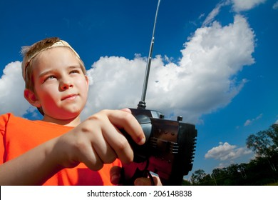 Little boy playing with RC toy outdoor under the clouds