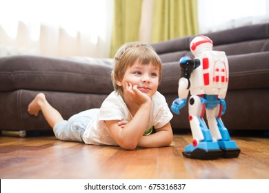 Little boy playing with robot toy at home