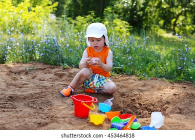 little boy playing with sand on playground