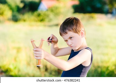 Little boy playing with slingshot at summer afternoon outdoors