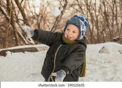 Little boy playing in the snow outdoors in winter.