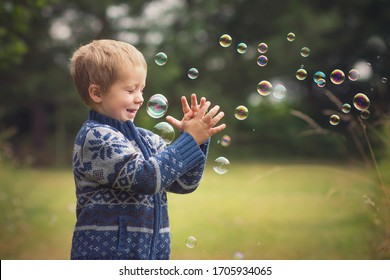 little boy is playing with soap bubbles in countyside