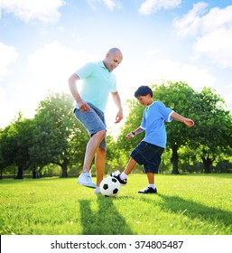 Little Boy Playing Soccer With His Father Concept