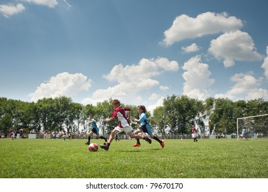 Little Boy playing soccer on the sports field