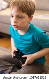Little boy playing some video games at home using a controller, making different expressions.