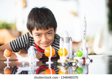 Little boy playing space ship and planet galaxy toy