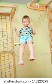 Little boy playing sports, swinging on a swing in his room.