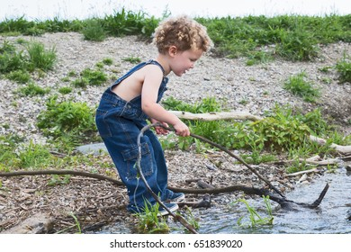 A little boy is playing with a stick in the water on a summer day. He is wearing overalls and not shirt. The child has blonde curls and is Caucasian. Playful summer fun.