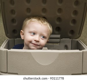 Little boy playing in a storage box