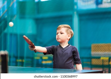 little boy playing table tennis indoors. hit the ball with a racket