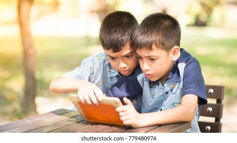 Little boy playing tablet game together in the park
