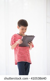 Little boy playing tablet at home