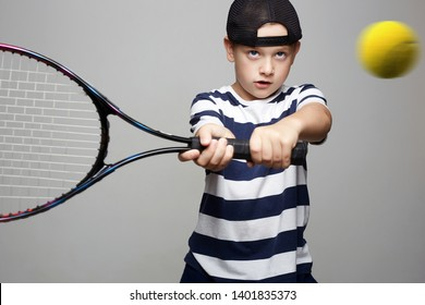 Little Boy Playing Tennis. Sport kid. Child with tennis racquet and ball