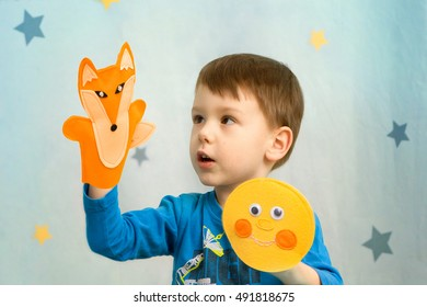 Little boy playing in the theater with hand puppet fox and Gingerbread Man