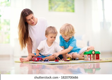 Little boy playing toy cars on play mat. Young kid with colorful educational vehicle and transport toys on carpet. City street map rug. Child driving car to parking garage. Kids at home or daycare.