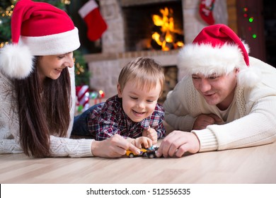 Little boy playing with toy cars with his parents under the christmas tree