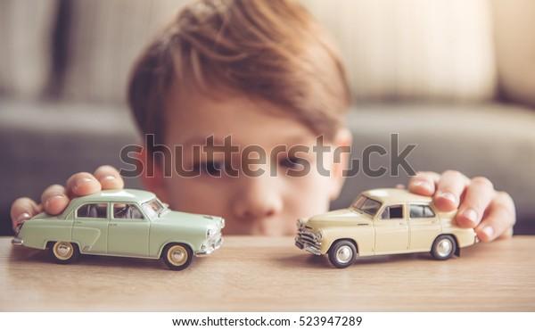 小さな少年は家でおもちゃの車で遊んでいる