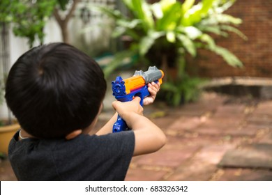 Little boy playing with a toy gun in the garden