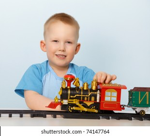 Little boy playing with a toy locomotive on blue background