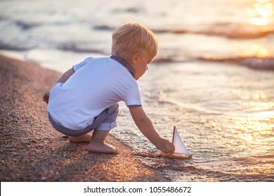 Little boy playing with toy seailing boat on sunset sea