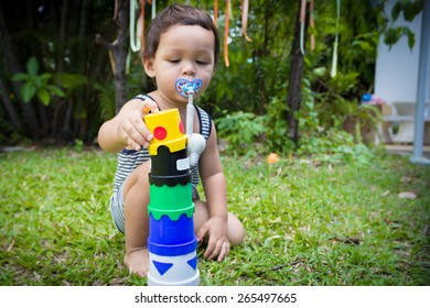 Little Boy Playing With A Toy Tower