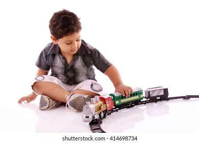 Little boy playing with toy train on white background