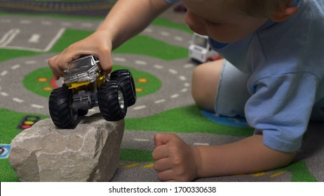 Little boy playing with toy truck car in his room alone. Child playing with toys (cars, trucks) indoor. Activities for kids at home