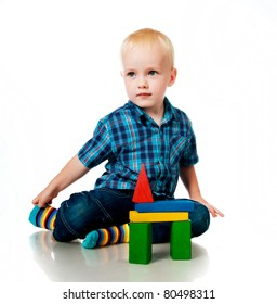 little boy playing with toys on a white background