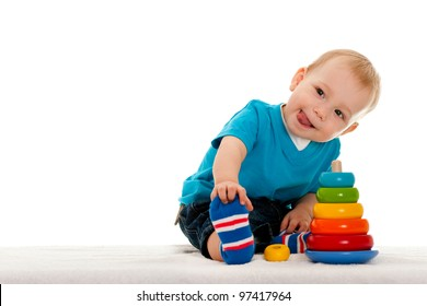 A little boy is playing with toys on the blanket; isolated on the white background