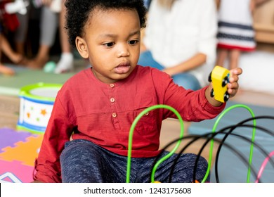 Little boy playing toys in the playroom